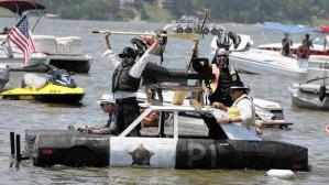 Left to right, Cameron Gembla, Tim Zableckis, Brandon Dobe, and Rodney Shipe paddle their Blues Brothers-themed boat in the Cedar Lake Summerfest. (Cedar Lake Summerfest, Handout)