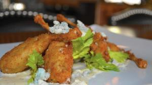 The new Hache Moderne Brasserie on State Street in Geneva offers an exciting twist on traditional French cuisine. Pictured here is the buffalo frog legs, topped with whipped Gorgonzola and celery leaves. (Beth Casey / Beacon-News)