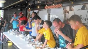 Contestants in the porkburger eating contest eat their hearts out at the Kouts Pork Fest. (Kouts Pork Fest / Handout)